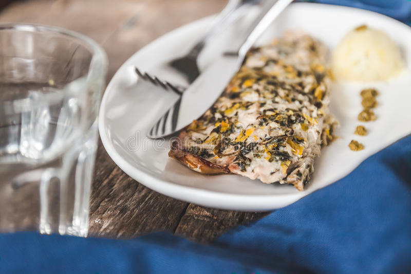 Fish mackerel baked with herbs, mashed potatoes, pesto sauce served on a white plate on a wooden antique background, next to a bl royalty free stock image