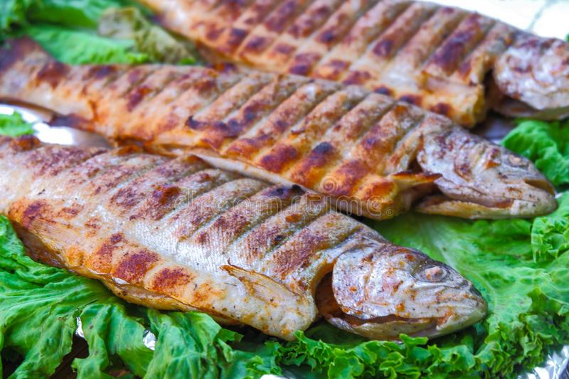 Fish mackerel on the grill on skewers with lemon royalty free stock images
