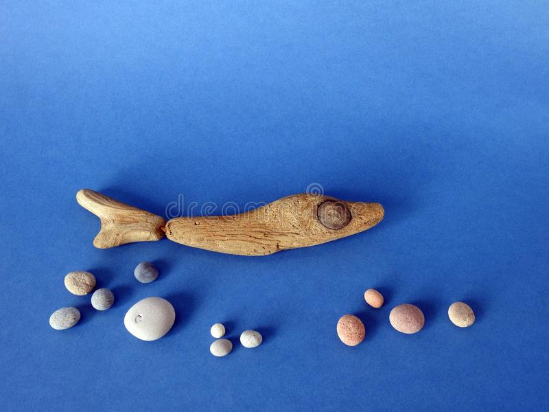 Fish made from sea wood on blue background stock photo