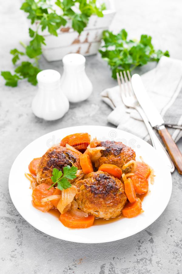 Fish meatballs or noisettes baked with carrot, onion and tomato sauce. Fish meatballs on plate stock photo
