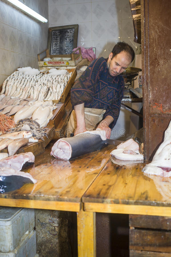 Fish monger cutting shark at his store in in Fez royalty free stock photography
