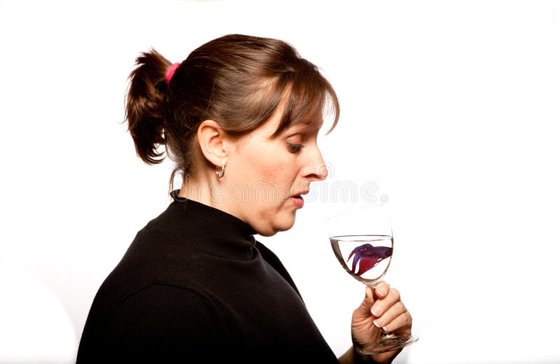 Fish in my Wine Glass. High Key shot of a woman dressed in a black turtleneck holding a white wine glass with a betta fish in it looking down royalty free stock photos