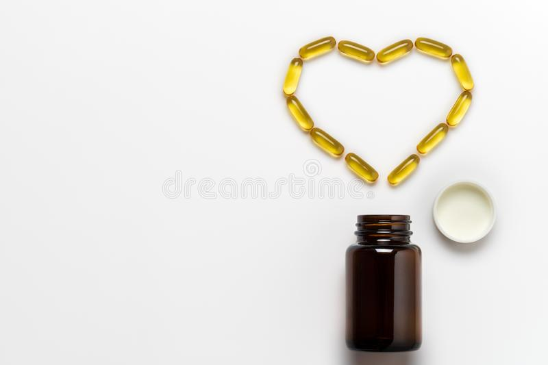 Fish oil capsule is arranged into the heart shape on white background. stock photography