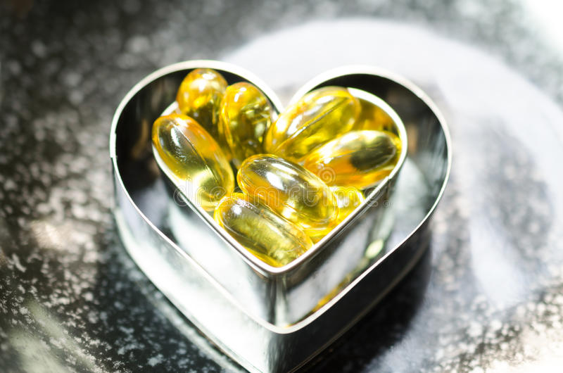 Fish oil capsule on double heart shape box in smaller one on bl stock photo
