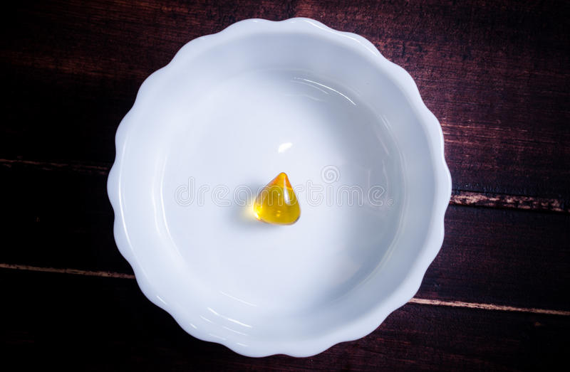 Fish oil gel capsule. Fish oil in pocelain bowl background royalty free stock photos