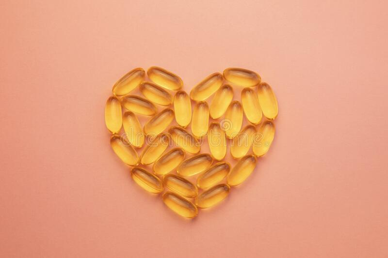Fish oil omega in soft capsules in heart shape on pink background, health and beauty concept. Fish oil omega in yellow soft capsules in heart shape on pink royalty free stock images