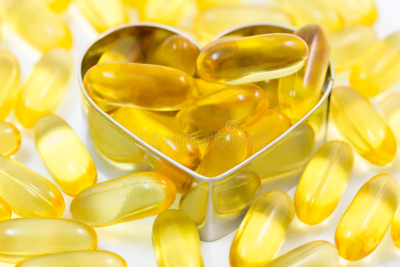 Fish oil pills on heart shape box royalty free stock photos