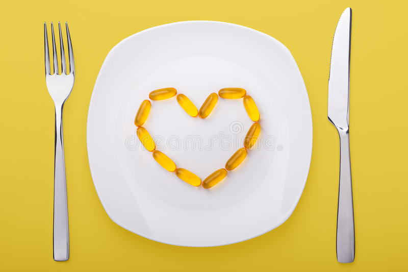 Fish oil soft gels lying on a plate royalty free stock image
