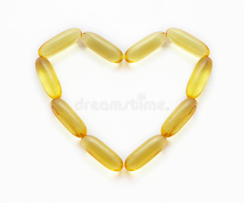 Fish oil supplements in a shape of a heart royalty free stock photography