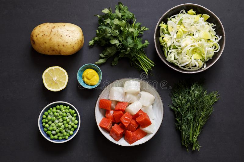 Fish pie ingredients on black background. Fish pie ingredients, leek, potato, salmon, haddock and herbs stock photo