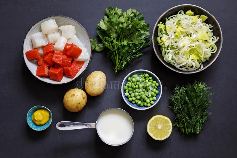 Fish pie ingredients on black background. Fish pie ingredients, leek, potato, salmon, haddock and herbs royalty free stock images