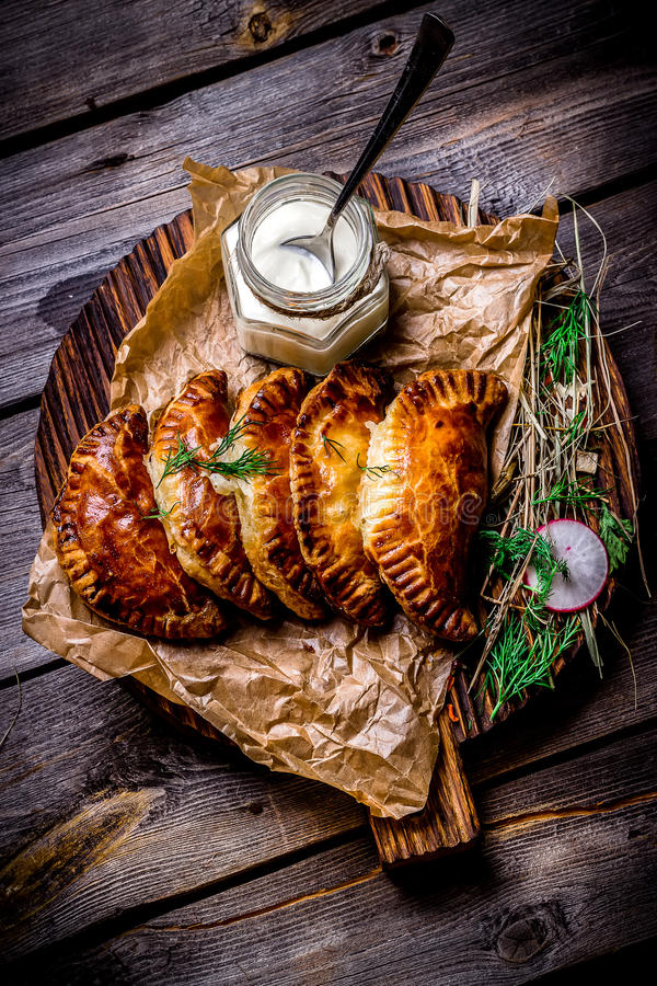 Fish pies and sour cream on a wooden chopping board, restaurant giving. Style rustic. Selective focus royalty free stock photos