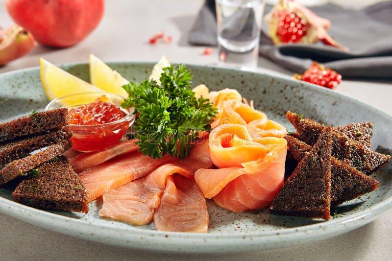Fish Platter with Light-Salted Salmon, Smoked Salmon, Red Caviar and Borodino Black Bread Toast royalty free stock photo