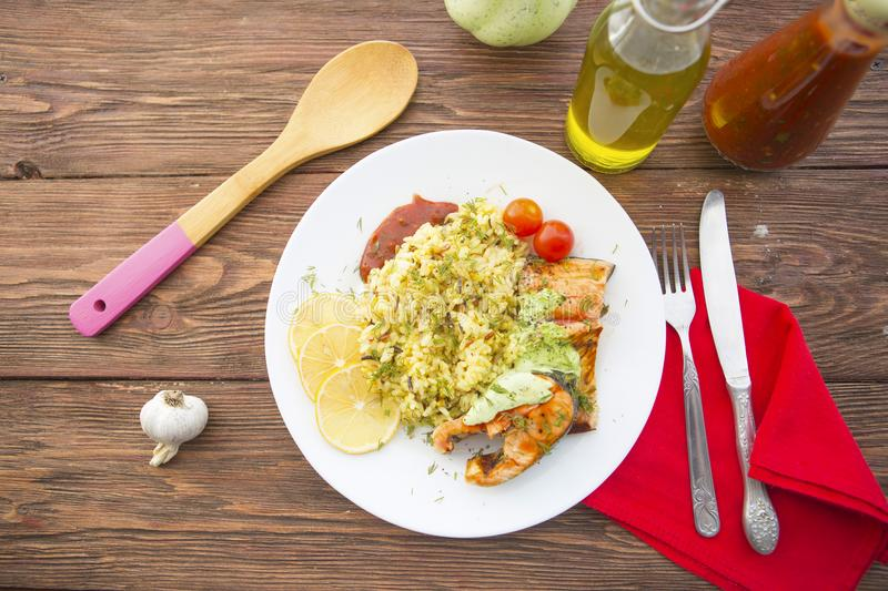 Fish with rise on plate on wooden table royalty free stock photography