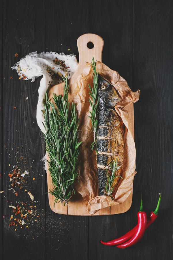 Fish with rosemary on parchment paper on a black wooden background, healthy food on kitchen table top view, grill seafood stock photography