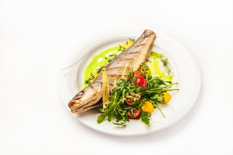 Fish and salad in a restaurant close-up. Dorado on a white plate and copy space royalty free stock photography