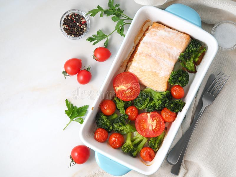 Fish salmon baked in oven with vegetables - broccoli, tomatoes. Healthy diet food, white marble backdrop, top view. Fish salmon baked in oven with vegetables stock photos