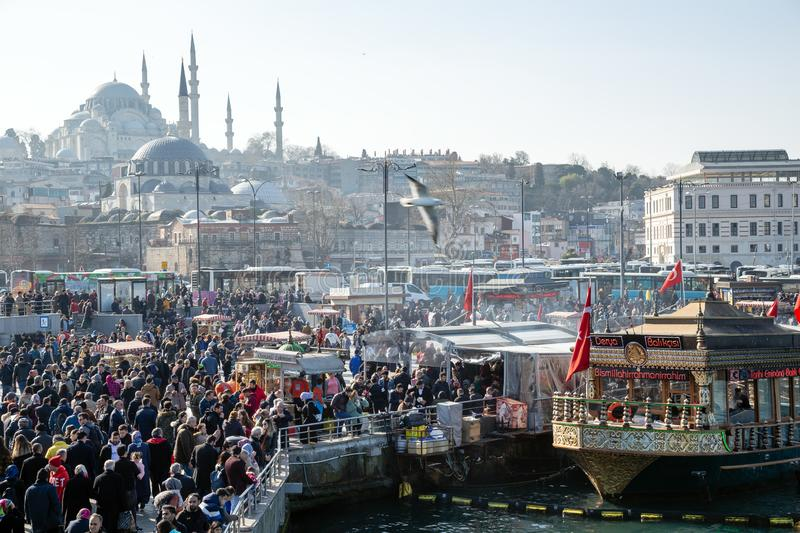 Fish sandwich shop boats in Eminonu Pier at to mouth of the Golden Horn Bay. Crowd of people outside in Eminonu Square, Istanbul, royalty free stock images