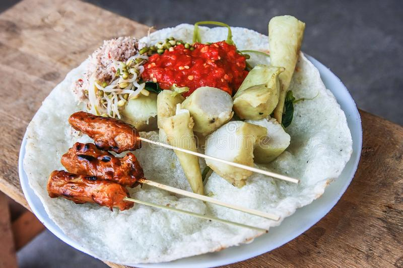 Sate Ikan Tanjung Fish Satay. Indonesian traditional food from Lombok called Sate Ikan Tanjung served With crackers, vegetables & rice cake stock photography