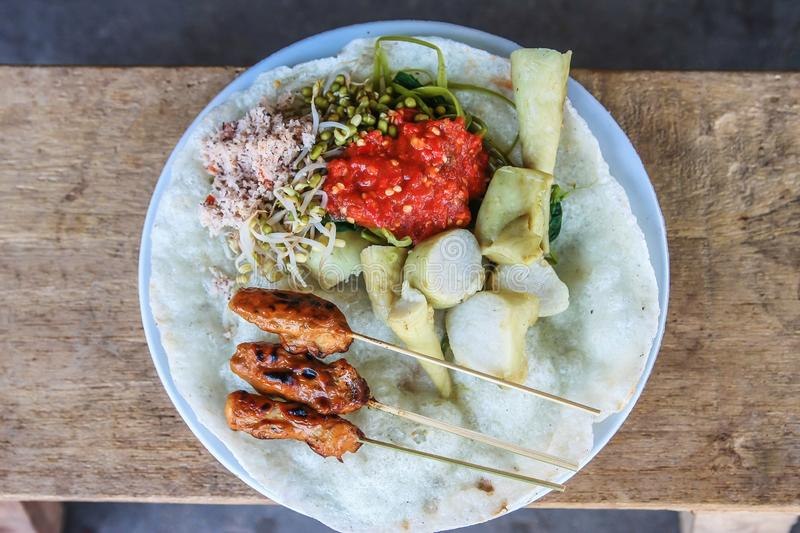 Sate Ikan Tanjung Fish Satay. Indonesian traditional food from Lombok called Sate Ikan Tanjung served With crackers, vegetables & rice cake royalty free stock image