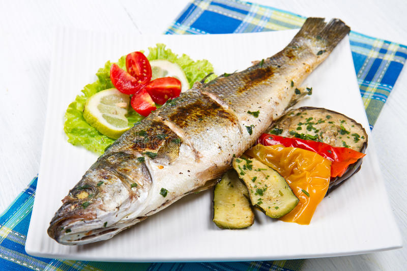 Fish, sea bass grilled with lemon and grilled vegetables stock image