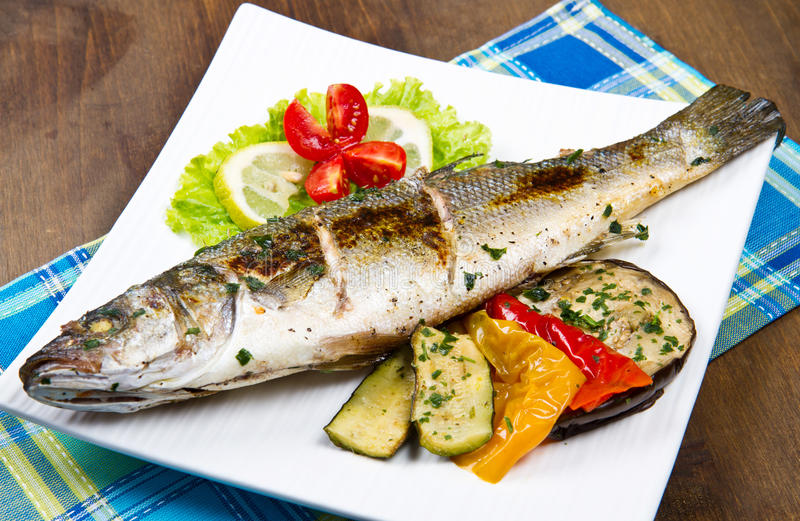 Fish, sea bass grilled. With lemon and grilled vegetables stock photos