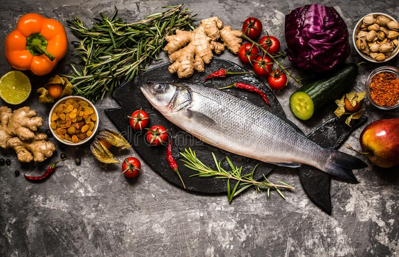 Fish, sea bass and ingredients for cooking: vegetables, spices royalty free stock photo