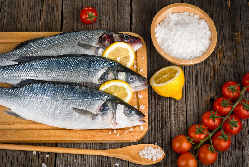 Fish sea bass with spices. Fish sea bass with salt, lemon on wooden hardboard, prepared for cooking royalty free stock image