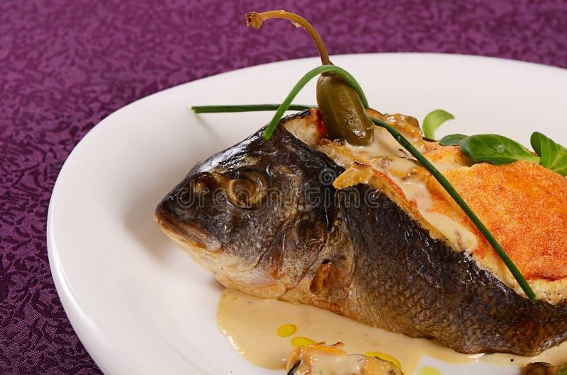 Fish sea bass stuffed with mushrooms. Sauce royalty free stock photo