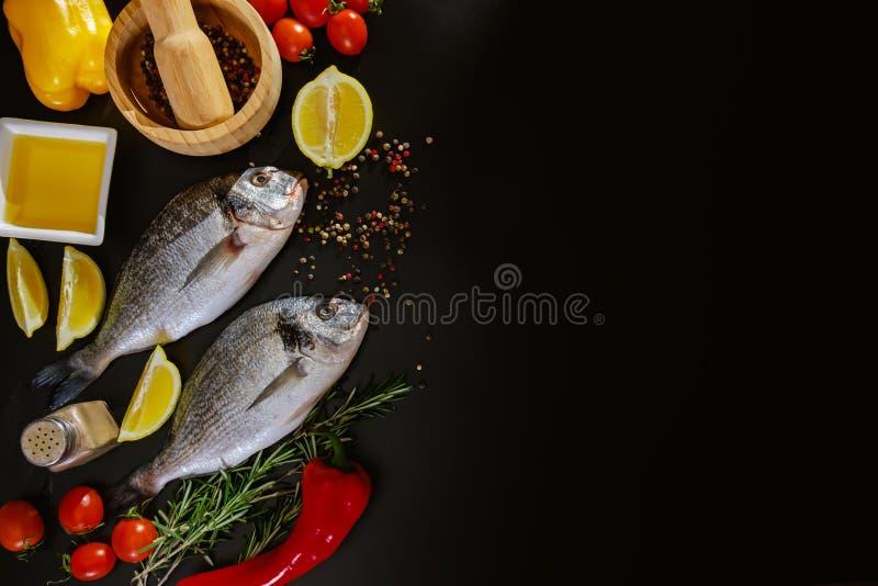Fish seafood dorado cooking, raw food on black background, background. Fish seafood dorado cooking, raw food on black background with ice and copy space royalty free stock photo