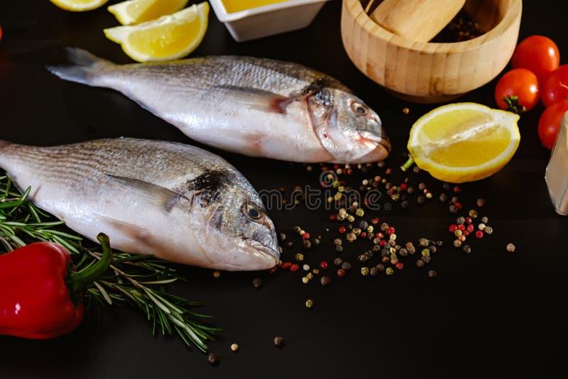 Fish seafood dorado, raw food on black background, lemon. Fish seafood dorado, raw food on black background with ice, lemon stock images