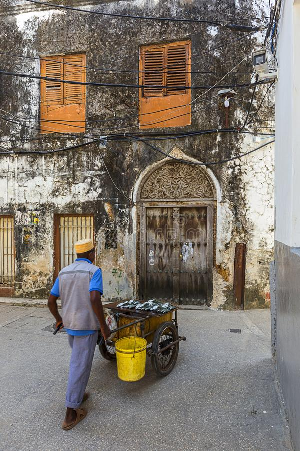 Fish seller on the stone town streets and alley-ways. Urban and city life with the movement on the rustic streets and alley-ways of the old town on zanzibar royalty free stock photography