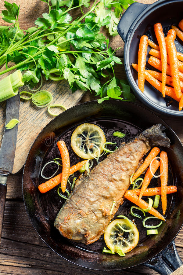 Fish served with carrots and lemon royalty free stock photography