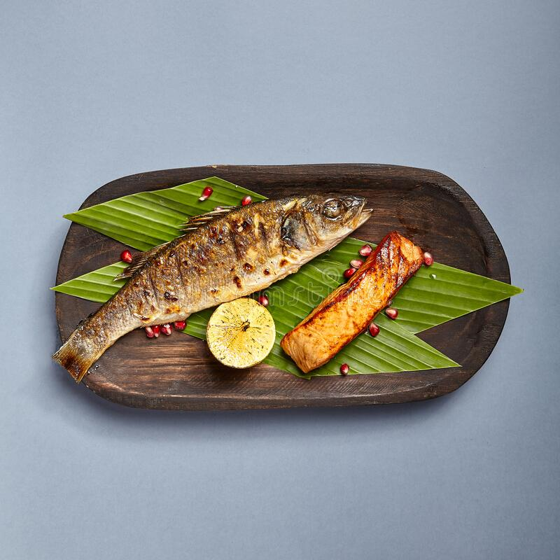 Fish served on wooden rustic plate royalty free stock images