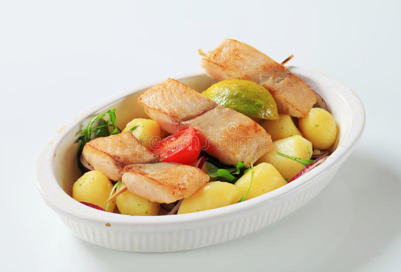 Fish skewer and potatoes. In casserole dish stock photo