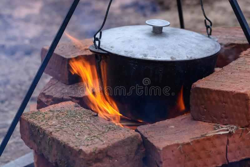 Fish soup boils in a cauldron on an open fire. Soup in a pot on a fire, picnic in nature stock images