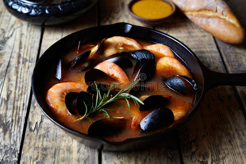 Fish soup bouillabaisse. Mussels and shrimp in tomato sauce. The traditional dish of Marseilles. Rustic style. Fish soup bouillabaisse. Mussels and shrimp in stock images