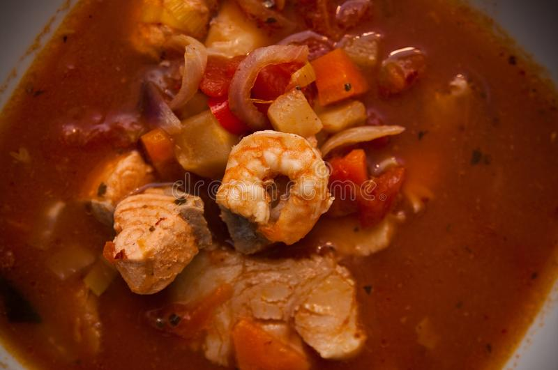 Fish soup with cod and prawns. Food photography: a spicy red fish soup with cod, paprika, spices and prawns or shrimps. Whole series with sebczseries1013 keyword royalty free stock images