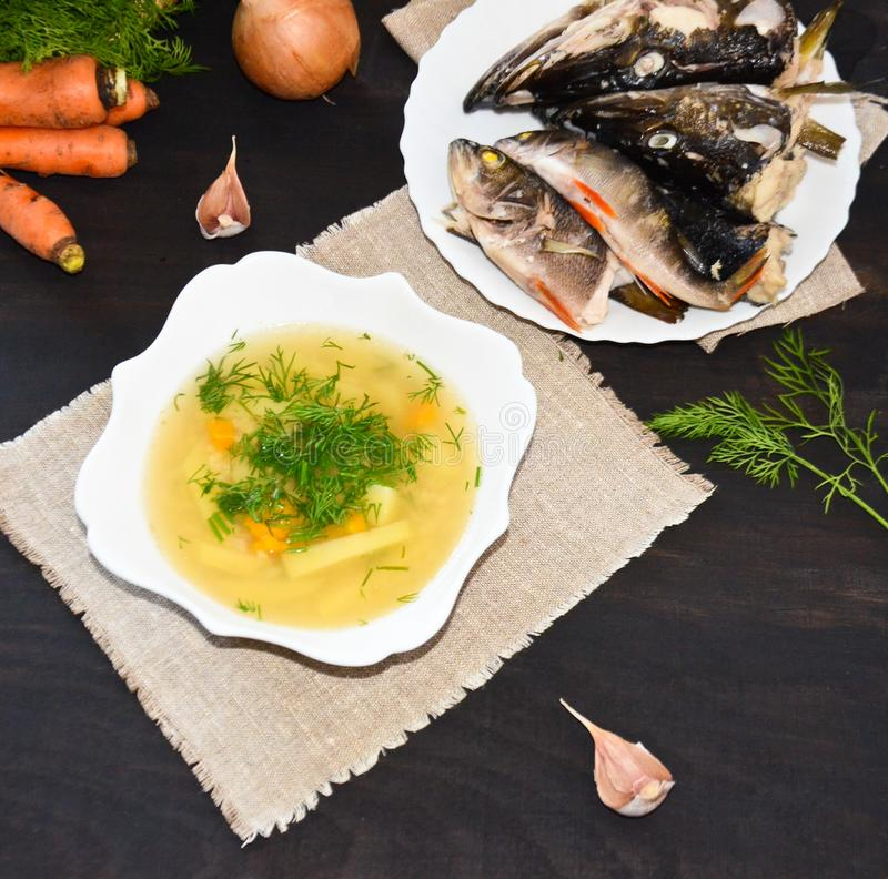Ukha fish soup in white plate on the heads of slaves and small fish and with carrots and greens on a black background royalty free stock image