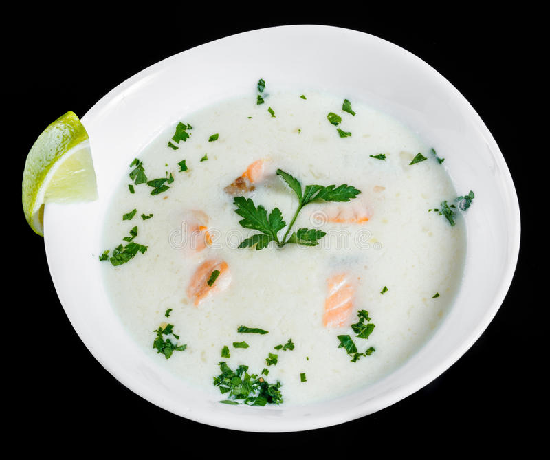 Fish soup with salmon and shrimps, parsley and lemon in bowl, isolated on black background, healthy food. royalty free stock photos
