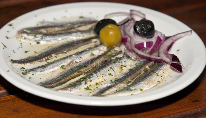Fish specialty. Mediterranean specialty - small fish in lemon sauce with olives served for eating stock photography