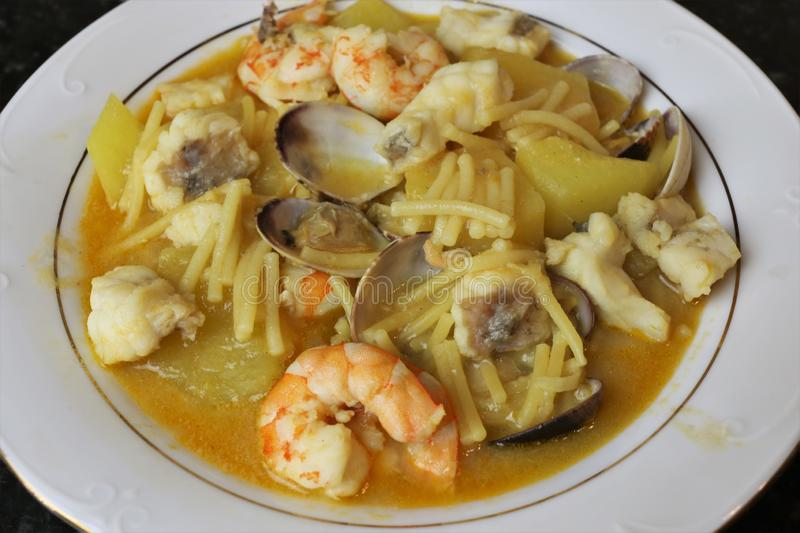 Fish stew with prawns and clams. The fish stew with prawns and clams is a typical meal of homemade Andalusian and Spanish cuisine. The stew is on a white plate royalty free stock images