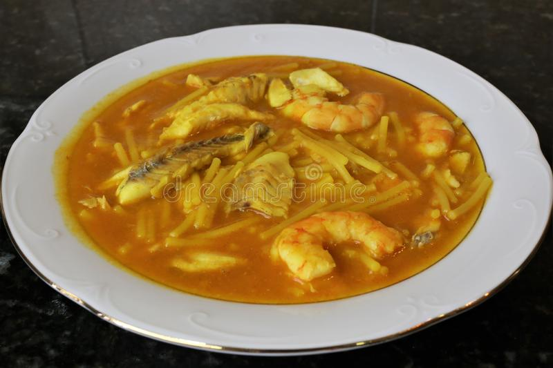 Fish stew with prawns and clams. The fish stew with prawns and clams is a typical meal of homemade Andalusian and Spanish cuisine. The stew is on a white plate royalty free stock photography