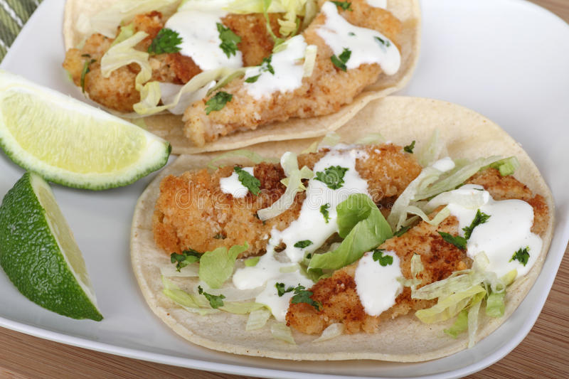 Fish Taco Meal. Two fish tacos on tortilla shells with sliced lime on a plate stock images