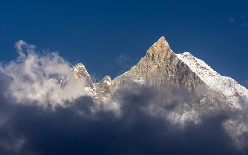 Fish Tail snowcapped summit rises among the clouds, Nepal stock photo