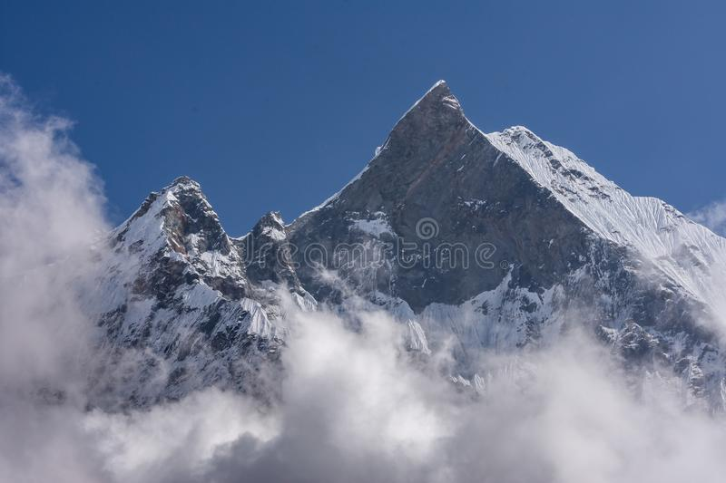 Fish Tail Summit also Machapuchare surrounded by rising clouds stock images