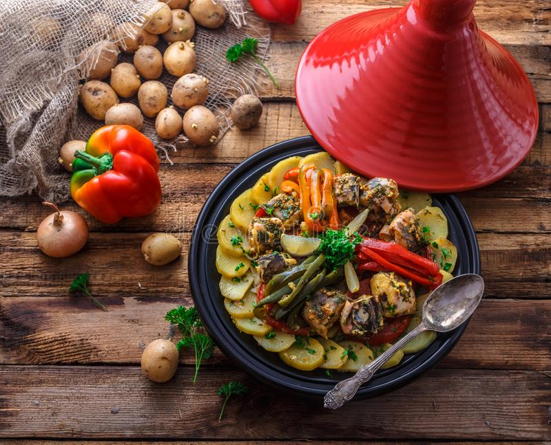 Fish tajine mqualli with potato and bell peppers, top view.  stock photo