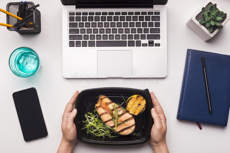 Fish in take away black box in woman hands on office table stock photos