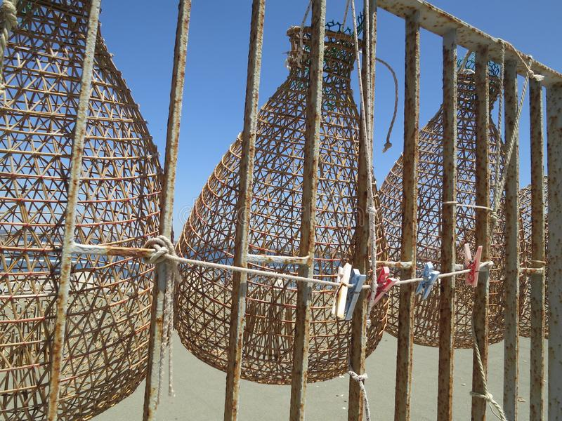 Fish trap made of reed. Hanging on an iron fence against blue sky stock images