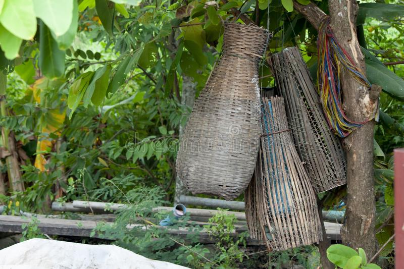 Fish trap under the tree. Tool for business of Fish Trap for rural villagers on the water area. Hanging under the tree stock photo